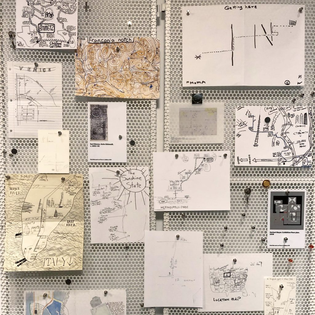 photograph of a wall with a variety of hand drawn maps